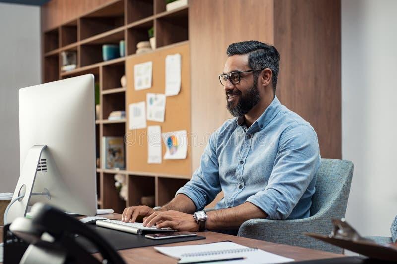 Творческий человек работая на компьютере стоковые изображения