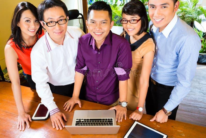 Творческое дело Азия - объединяйтесь в команду встреча в офисе стоковое изображение