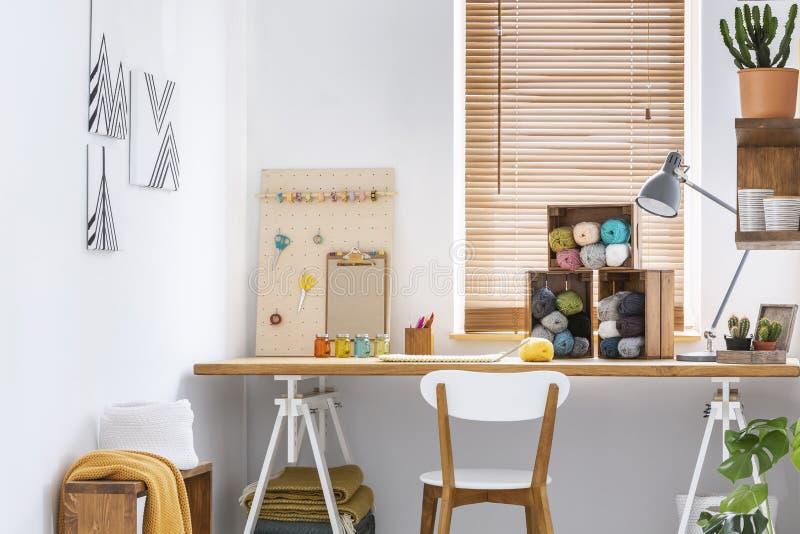 Творческое место для работы с скандинавской, деревянной мебелью, белыми стенами и шить инструментами в современном интерьере комн стоковые изображения