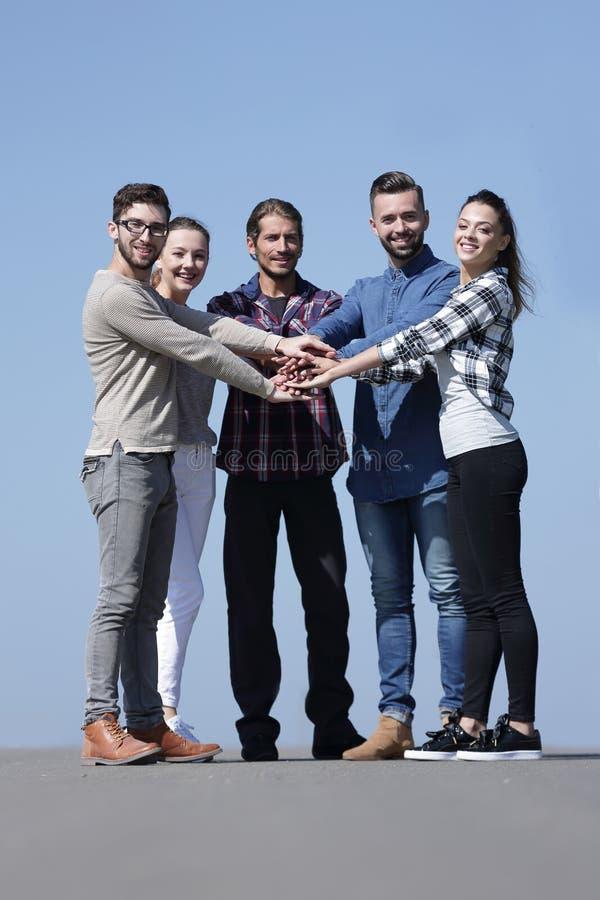 Творческое молодые люди сжимано их рукам совместно стоковое фото