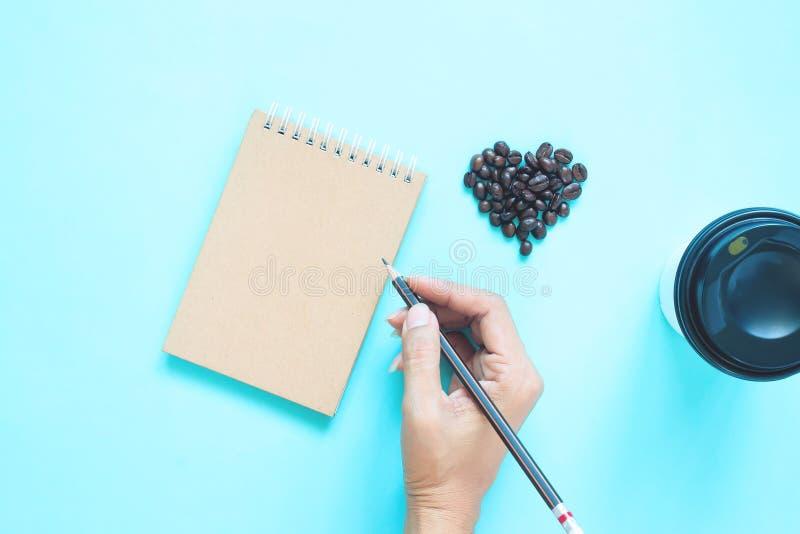 Творческое плоское положение кофейных зерен формы сердца и карандаша удерживания руки женщины с тетрадью на голубом цвете стоковые фото