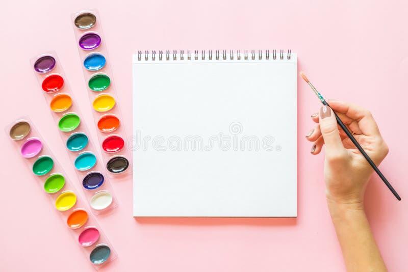 Творческое плоское положение палитр акварели, тетрадь, женская кисть удерживания руки Рабочее место художника на розовой пастельн стоковые фото
