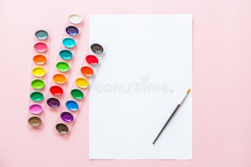 Творческое плоское положение палитр акварели, brushe краски, белая бумага Рабочее место художника на розовой пастельной предпосыл стоковая фотография