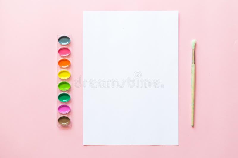 Творческое плоское положение палитр акварели, brushe краски, белая бумага Рабочее место художника на розовой пастельной предпосыл стоковые изображения rf