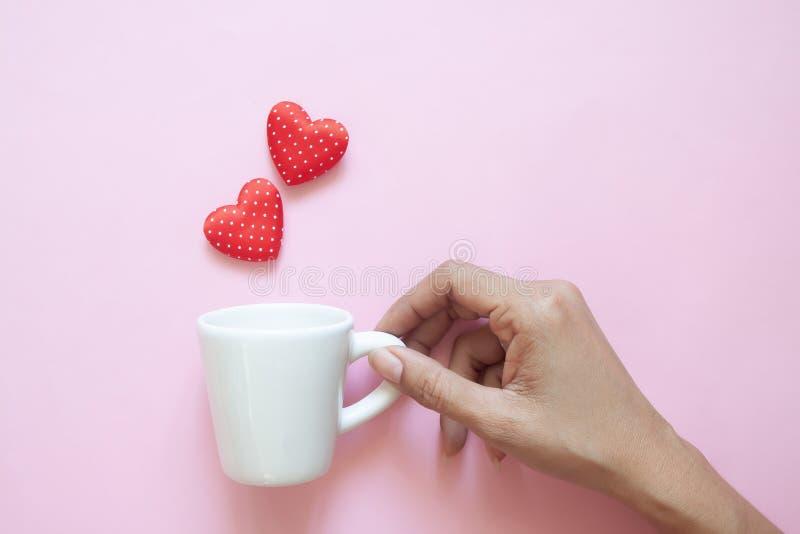 Творческое плоское положение, рука женщины держа белую чашку с сердцами точек польки красными на розовой предпосылке стоковые изображения rf