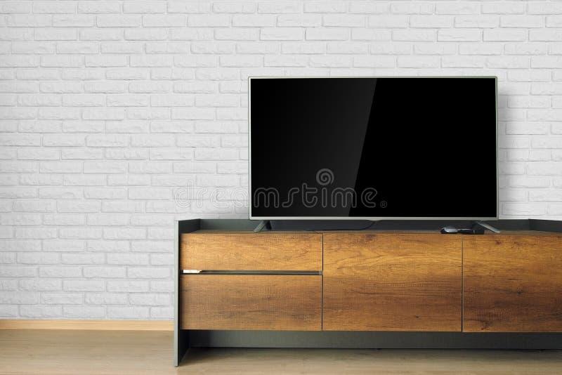 ТВ приведенное на стойке ТВ в пустой комнате с белой кирпичной стеной украсьте стоковое фото