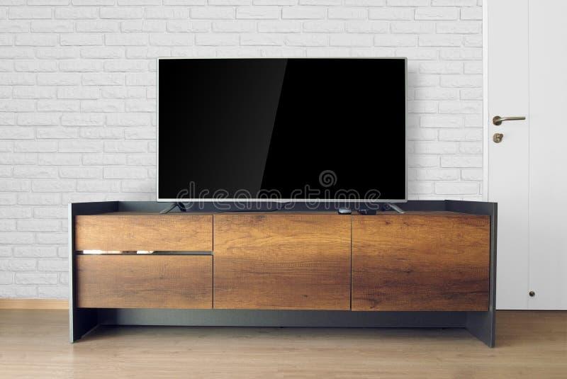 ТВ приведенное на стойке ТВ в пустой комнате с белой кирпичной стеной украсьте стоковое фото rf