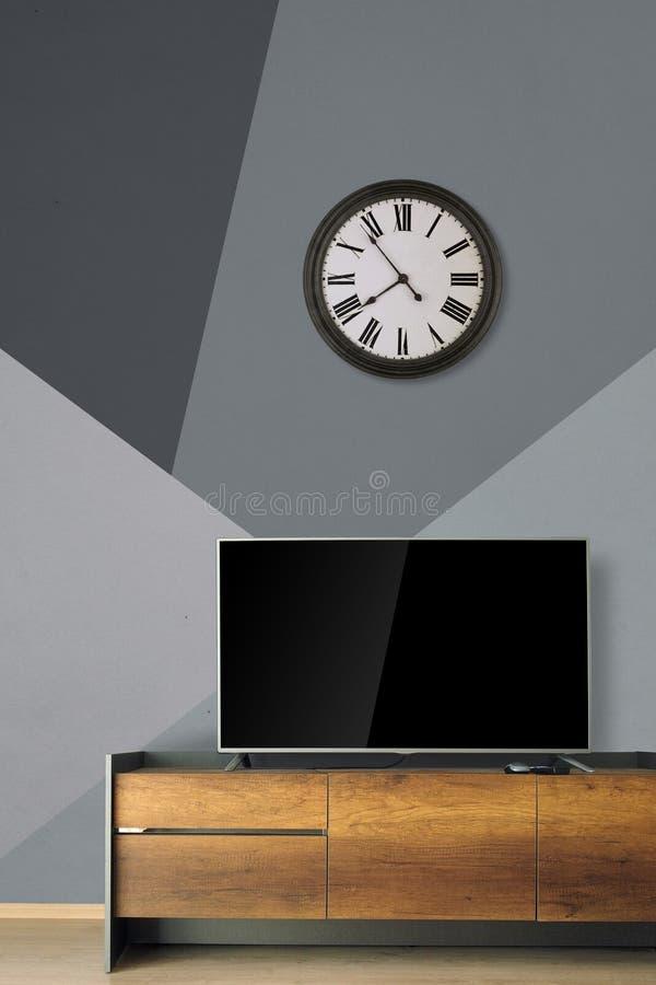 ТВ приведенное на стойке ТВ в пустой комнате с винтажными часами на современном wa стоковое изображение