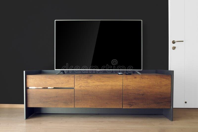 ТВ приведенное на стойке ТВ в пустой комнате с черной стеной украсьте в lo стоковые фото