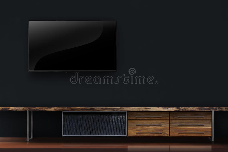 ТВ приведенное на черной бетонной стене с интерьером деревянного стола стоковое фото rf