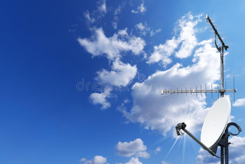 ТВ спутниковой антенна-тарелки и антенны на голубом небе стоковые изображения rf
