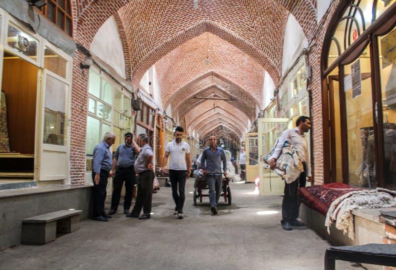 Тебриз, Иран - 10-ое июля 2017: Самый большой рынок мира в Тебризе, полный людей покупая в мусульманских магазинах Арабский базар стоковые изображения