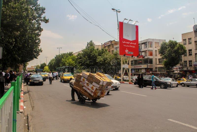 Тебриз, Иран - 10-ое июля 2017: Улица Ирана с несущей в середине дороги с автомобилями вокруг Гай поставляя cardbox внутри стоковое изображение