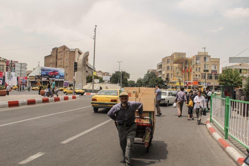 Тебриз, Иран - 10-ое июля 2017: Улица Ирана с несущей в середине дороги с автомобилями вокруг Гай поставляя cardbox внутри стоковое фото rf