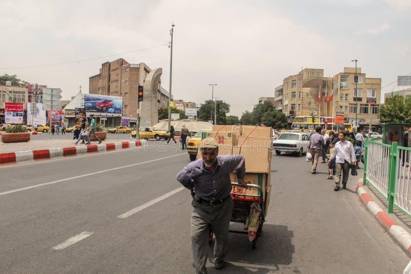 Тебриз, Иран - 10-ое июля 2017: Улица Ирана с несущей в середине дороги с автомобилями вокруг Гай поставляя cardbox внутри стоковое изображение rf