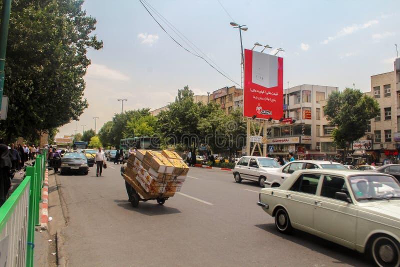 Тебриз, Иран - 10-ое июля 2017: Улица Ирана с несущей в середине дороги с автомобилями вокруг Гай поставляя cardbox внутри стоковые фотографии rf