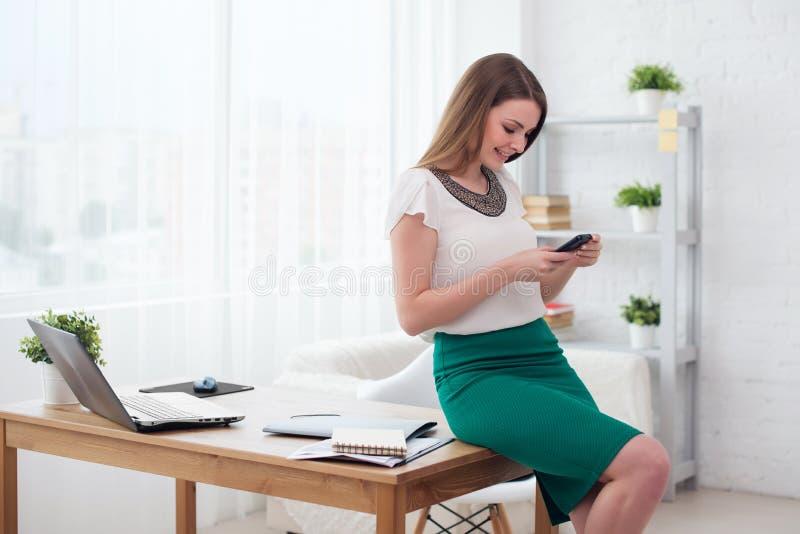 Текстовое сообщение бизнес-леди печатая на умном телефоне в таблице офиса сидя стоковое изображение rf