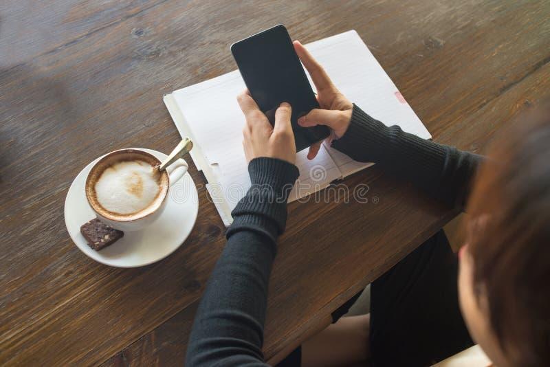 Текстовое сообщение молодой женщины на smarphone с обеими руками стоковые фото