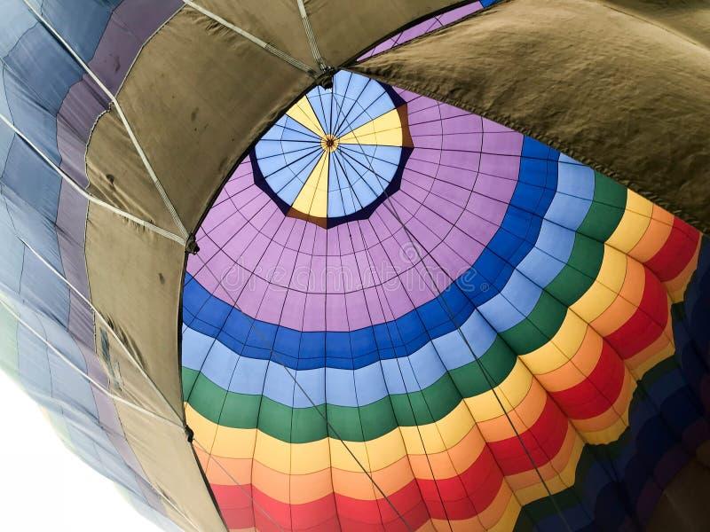 Текстура, взгляд от внутренности купола большой пестротканый яркий круглый радужный покрашенный striped воздушный шар летая стоковая фотография