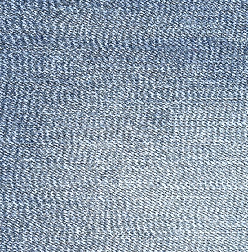 Текстура джинсовой ткани, свет - предпосылка голубых джинсов стоковые изображения
