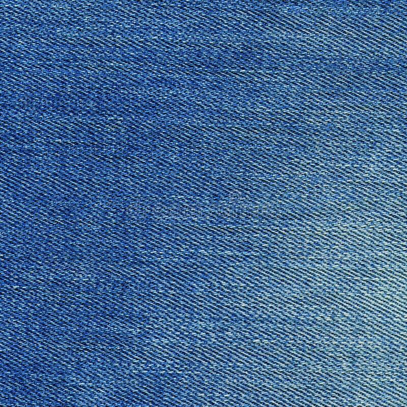 Текстура джинсовой ткани, свет - предпосылка голубых джинсов Поверхность конца-вверх джинсов голубая творческая стоковые изображения