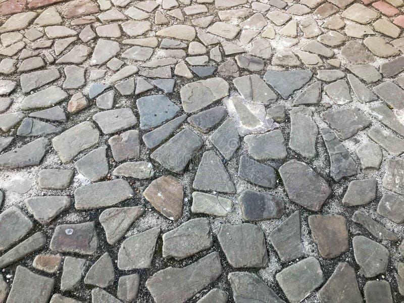 Текстура каменной дороги, мостовой, стен камней большого серого старого средневекового круга сильных, булыжников зелень gentile п стоковые фотографии rf