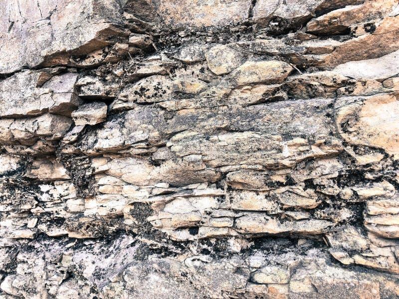 Текстура каменной стены острой треснутой выпуклой грубой естественной серой слойки старых старых каменных кирпичей в утесе стоковое изображение rf