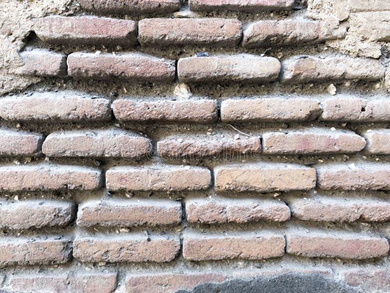 Текстура кирпича старого узкого выпуклого камня старого винтажного средневекового пылевоздушного подлинного коричневого со швами  стоковая фотография rf