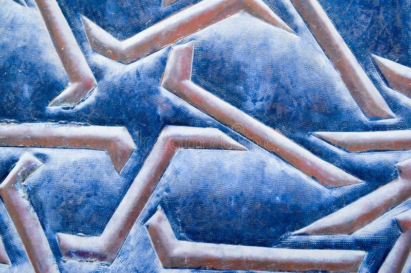 Текстура красивых аравийских звезд и коричневых выпуклых линий, нашивок и картин на голубой старой несенной резиновой ткани стоковая фотография