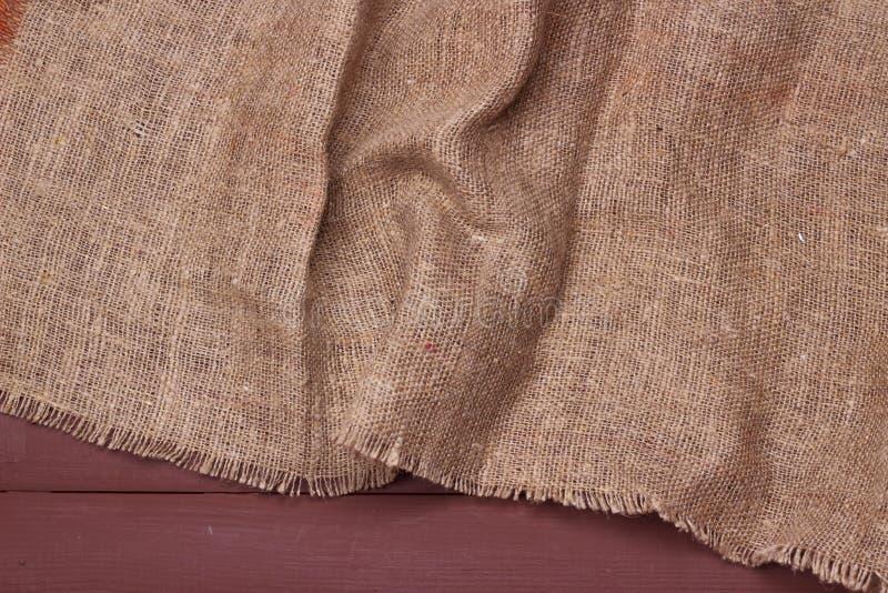 Текстура мешковины на предпосылке деревянного стола стоковые изображения