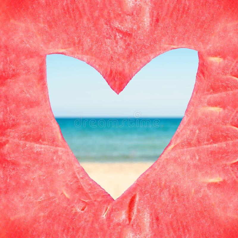 Текстура огромной зрелой части арбуза с отверстием формы сердца на предпосылке моря стоковые изображения