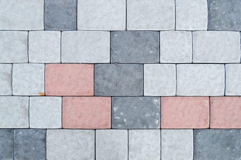 Текстура плит серого прямоугольного конкретного камня вымощая на дороге со швами зелень gentile предпосылки абстракции стоковое фото