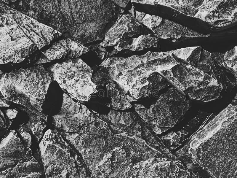 Текстура предпосылки каменной стены утесов в серых, черных белых цветах стоковые фотографии rf