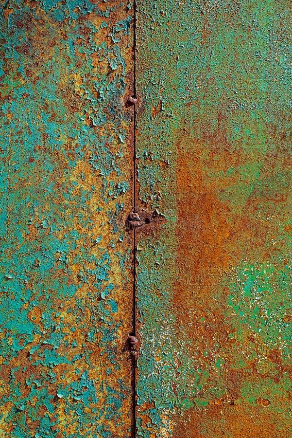 Текстура ржавого металла, покрашенный зеленый цвет который апельсин becames от текстуры ржавчины вертикальной треснутой краски на стоковые изображения rf