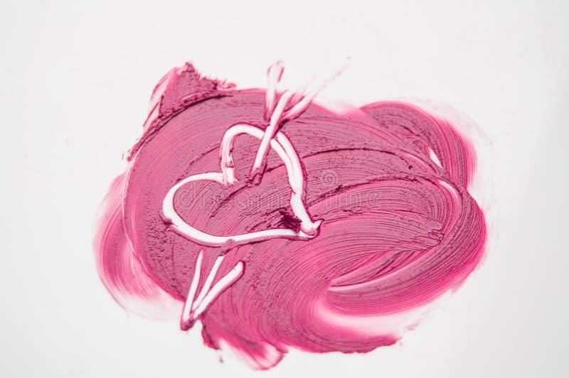 Текстура розовой сердца нарисованного губной помадой прокалыванного стрелкой, влюбленности, обжуливая, состава стоковые фото