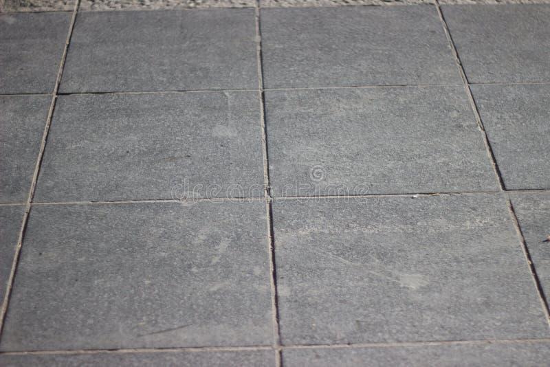 Текстура серого квадрата вымощая плитки на всей рамке стоковые фото