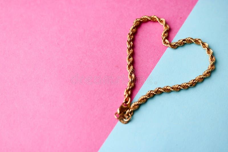Текстура соткать красивой золотой праздничной цепи уникальный в форме сердца на космосе предпосылки и экземпляра пинка пурпурном  стоковые изображения