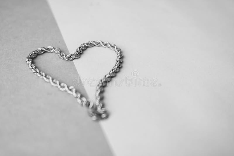 Текстура соткать красивой золотой праздничной цепи уникальный в форме сердца на черно-белом месте предпосылки и экземпляра стоковые изображения rf