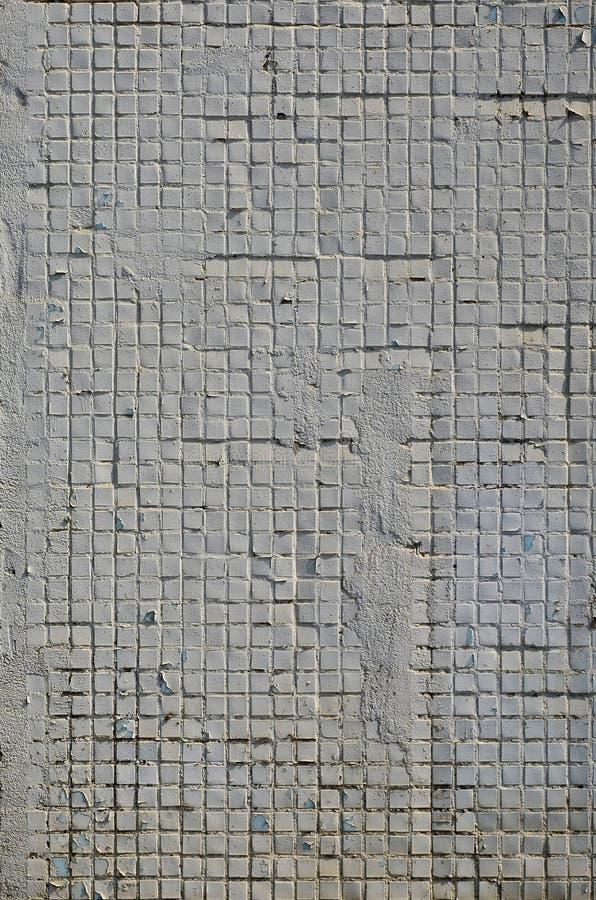 Текстура старой бетонной стены, с покрытием отмелых плиток квадратной формы, покрашенных в сером цвете Фоновое изображение wal стоковые изображения