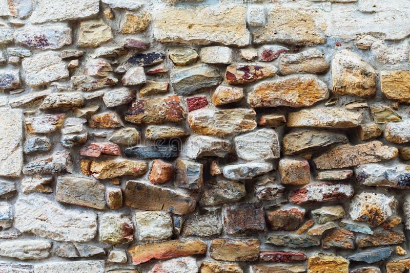 Текстура старой стены покрытой с различными камнями стоковое фото