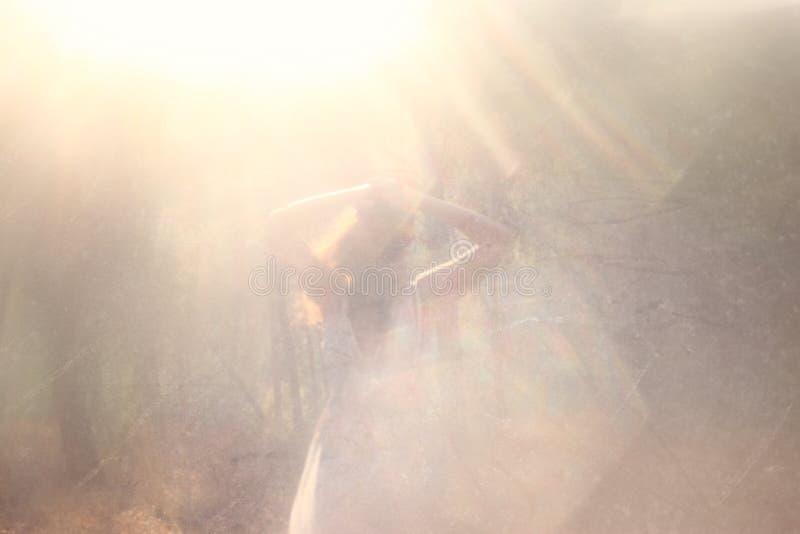 Текстурировано и тонизировано сюрреалистическое фото молодой женщины стоя в изображении леса Мечтательная концепция стоковое фото rf