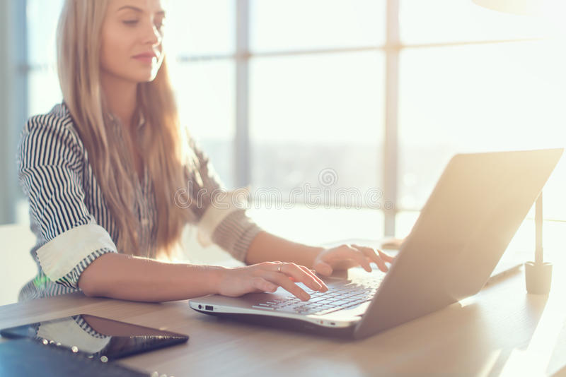 Тексты и блоги молодого красивого женского copywriter печатая в просторном светлом офисе, ее рабочем месте, используя клавиатуру  стоковое фото rf