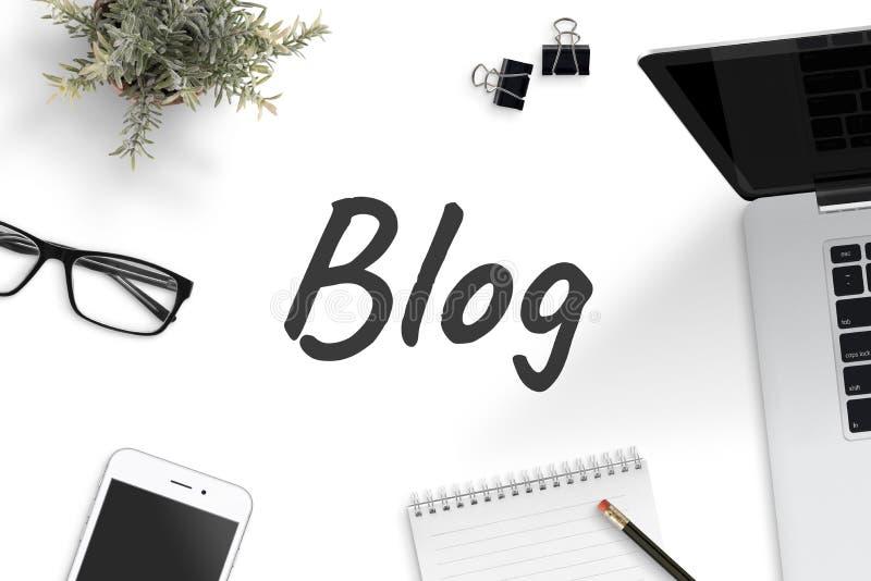 Текст блога на столе офиса окруженном с блокнотом, ноутбуком, умным телефоном, карандашем, зажимами, стеклами, заводом стоковые фото
