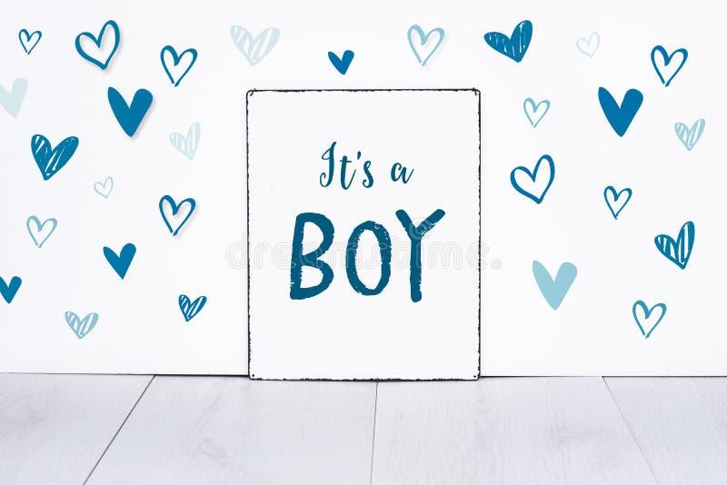 Текст младенца новорожденного мальчика на доске знака с милыми маленькими голубыми сердцами на белой предпосылке стоковое фото rf