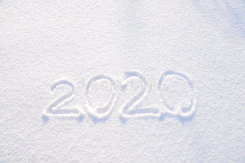 текст 2020 написанный на предпосылке свежей текстуры снега - зимнего отдыха, веселого рождества, дня концепции Нового Года солнеч стоковые фотографии rf