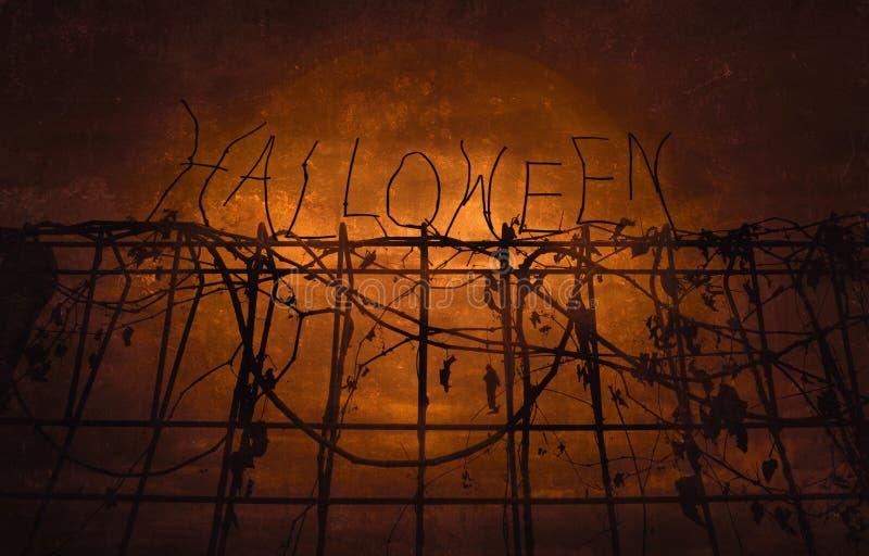 Текст над загородкой металла с сухими листьями над темным небом, h хеллоуина стоковые изображения