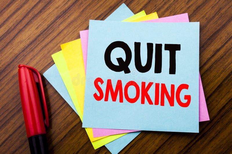 Текст объявления почерка прекратил курить Концепция для стопа для сигареты написанной на липкой бумаге примечания ручки с деревян стоковые изображения