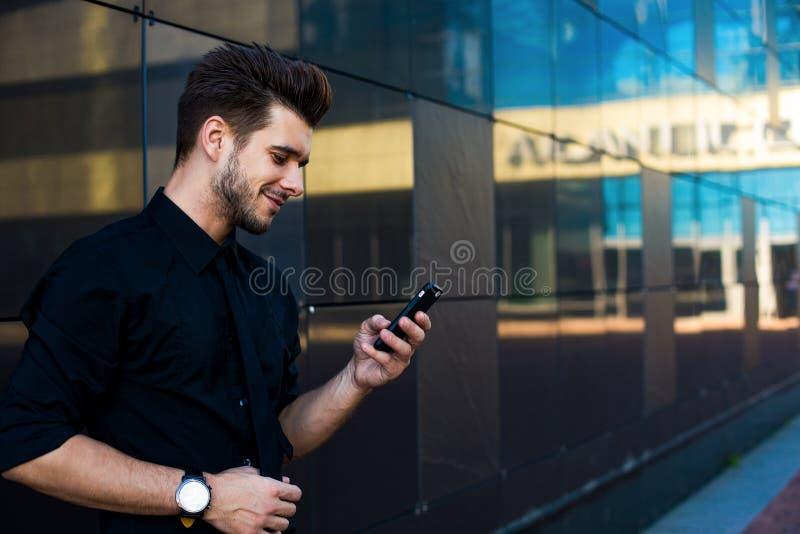 Текст парня хипстера печатая на смартфоне во время онлайн учить на netbook стоковые изображения