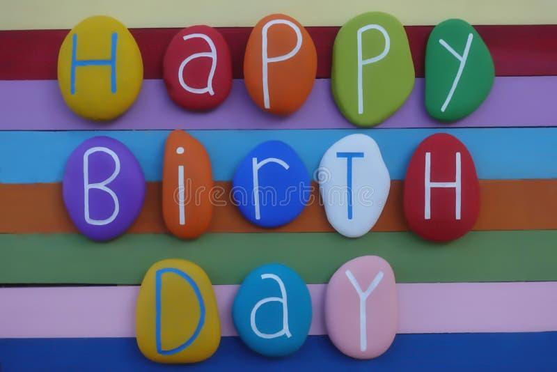 Текст с днем рождений с покрашенными камнями над multi покрашенной деревянной доской стоковое фото rf