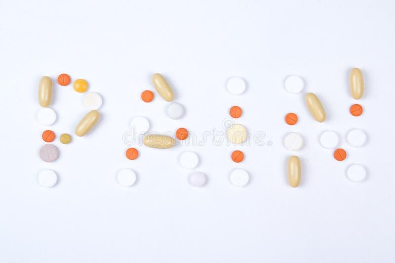 Текст слова боли сделанный из красочных таблеток стоковое фото rf